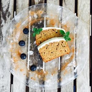 gâteau à la carotte présenté dans une assiette transparente, deux tranches avec myrtille et feuilles de menthe